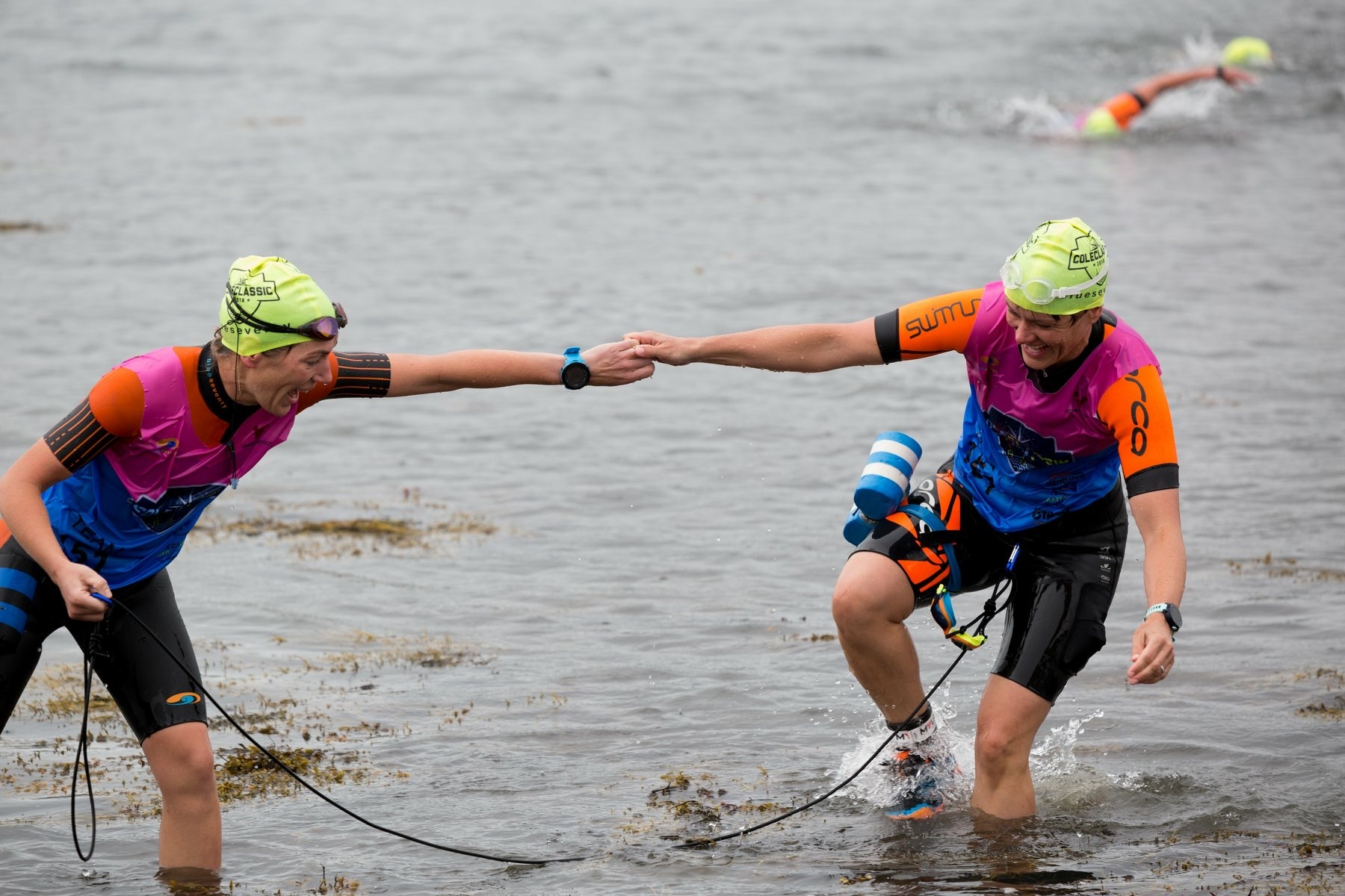 how swimrun is different from triathlon: two swimrunners exiting water