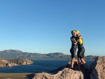 Two swimrunners hugging on a mountain top