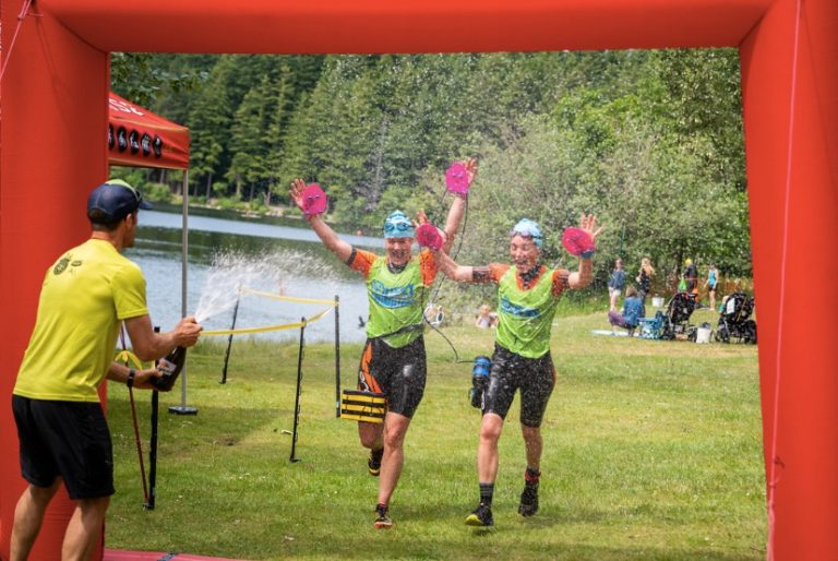 Brooke and Annie crossing the finish line with champagne being sprayed in their faces