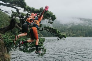 Brooke and Annie leaping off cliff at Orcas Island Swimrun