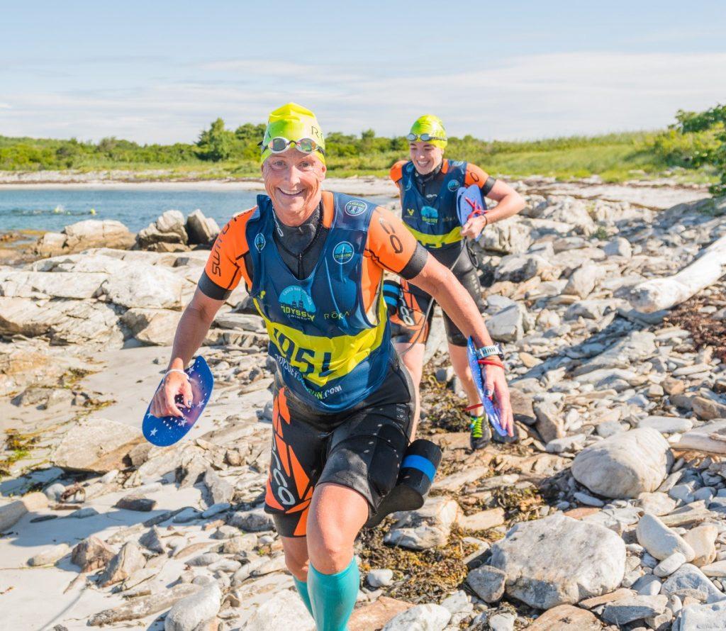 Two female swimrunners crossing a rocky island