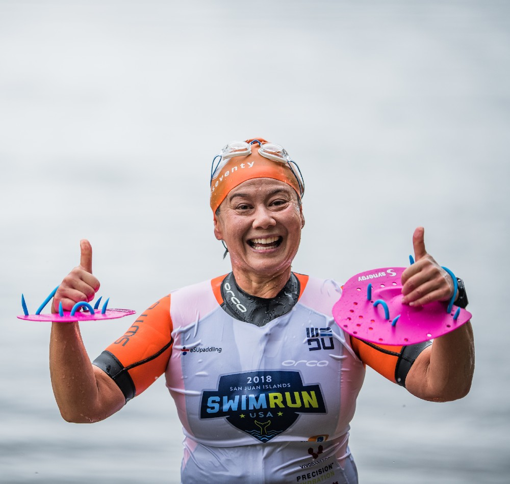 Female swimrunner exiting the water smiling and giving two thumbs up