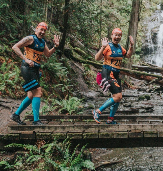 two female swimrunners crossing wooden bridge over stream with waterfall in background